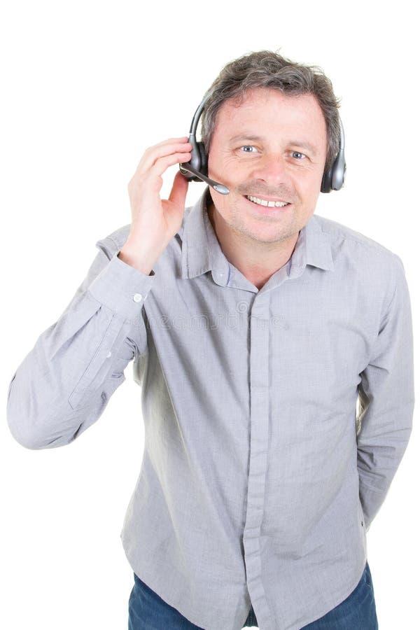 Усмехаясь человек оператора телефона работы с клиентом в центре телефонного обслуживания в белой предпосылке стоковые изображения rf
