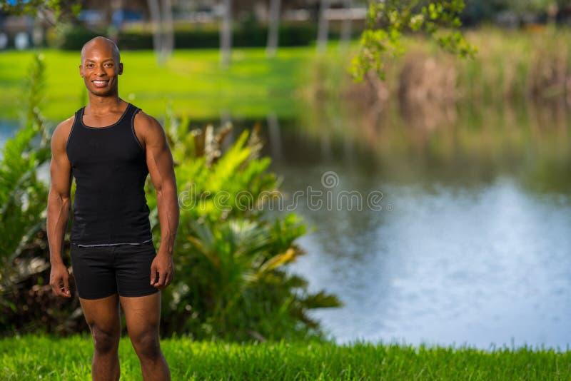Усмехаясь человек представляя озером в парке стоковое фото rf