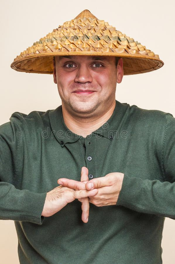 Усмехаясь человек при азиатская соломенная шляпа показывая странную руку подписывает стоковое фото rf