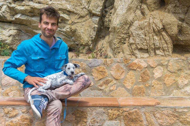 Усмехаясь человек счастливый держащ его принятого смешанного далматинского щенка и сидящ на каменном стенде Концепция принятия лю стоковое фото rf