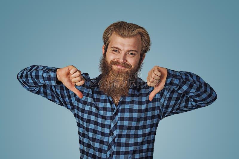 Усмехаясь человек с большим пальцем руки вниз Жизнерадостный парень выражая неутверждение стоковое изображение rf