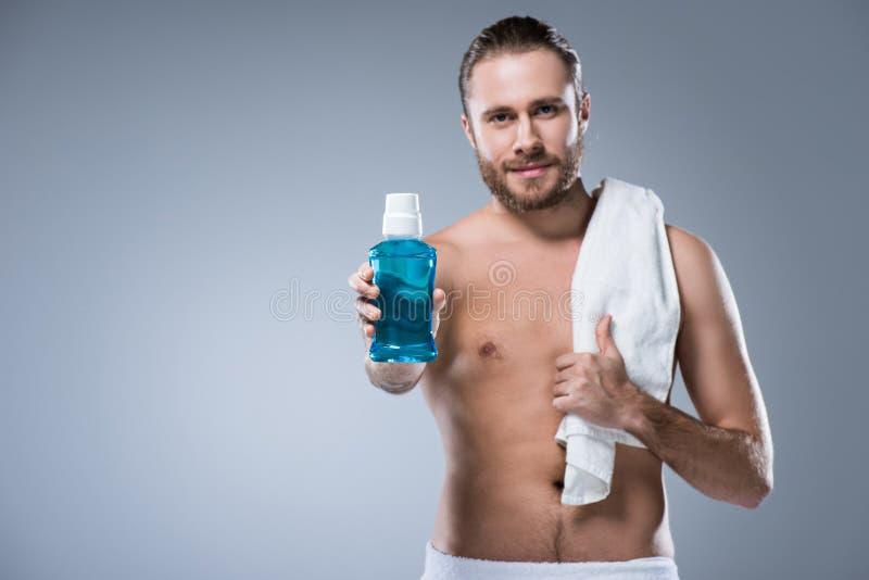 Усмехаясь человек с полотенцем ванны на плече держа бутылку с rinse зуба в протягиванной руке, стоковая фотография