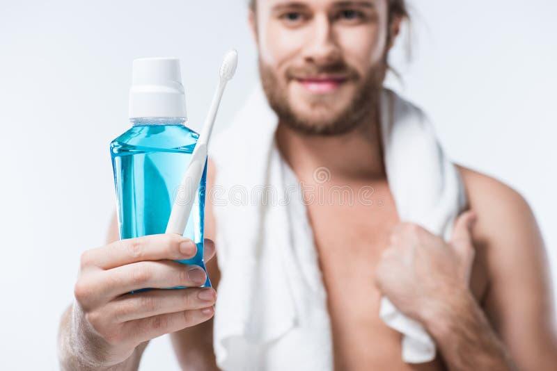 Усмехаясь человек с полотенцем вокруг его шеи держа зуб полощет и зубная щетка в руке, стоковое изображение rf