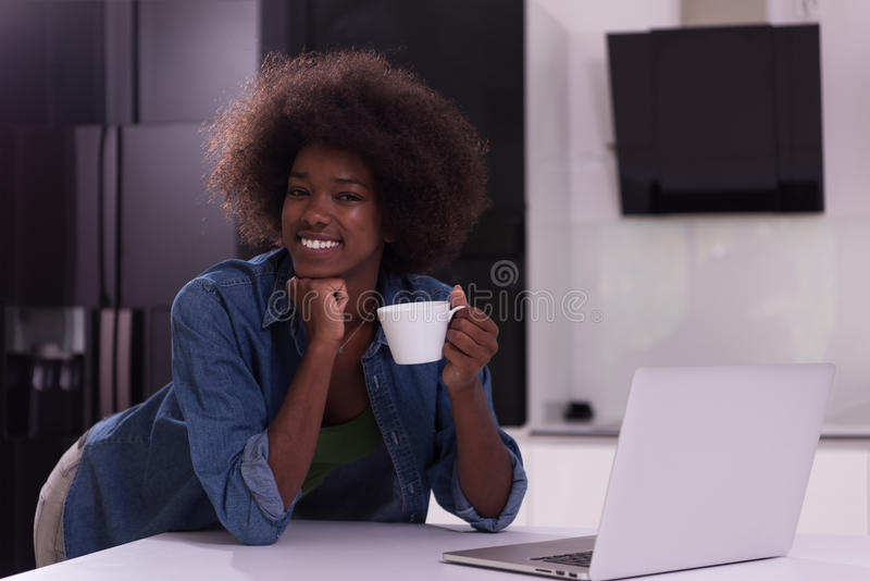 Усмехаясь чернокожая женщина в современной кухне стоковые фото