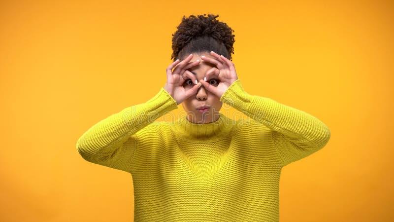 Усмехаясь чернокожая женщина делая стороны на желтой предпосылке, име стоковое фото rf