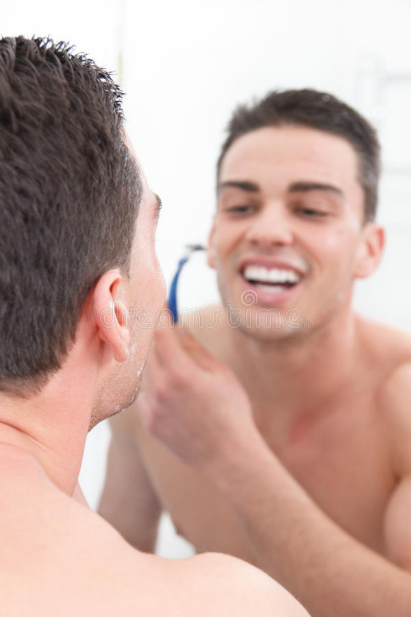 Усмехаясь человек брея в ванной комнате получая готовый на день стоковые фото