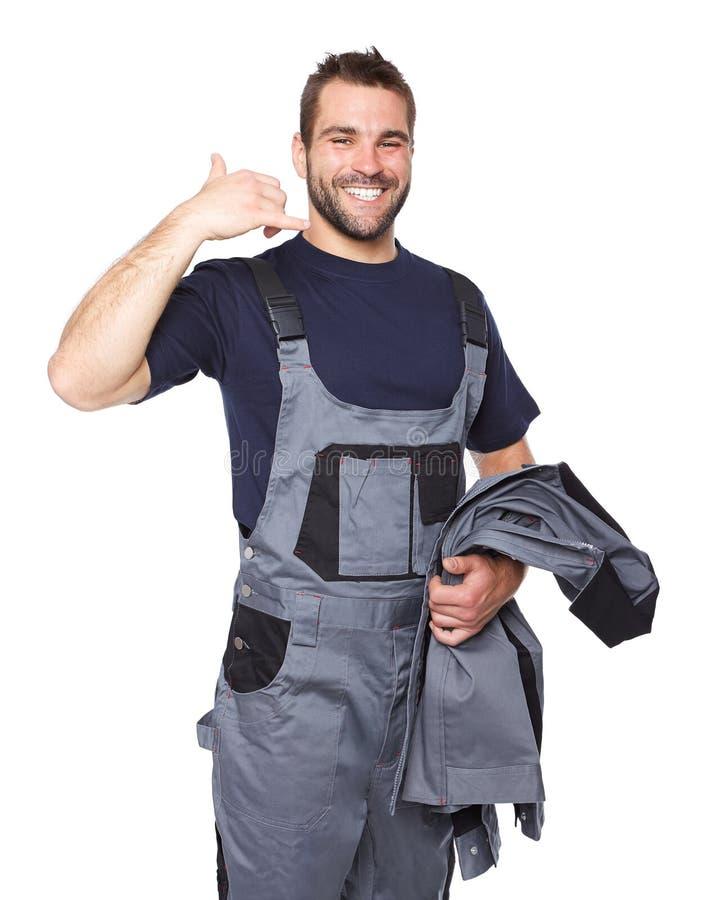 Усмехаясь человек в рабочей одежде делая звонком меня знак ...
