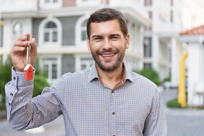 Усмехаясь человек задерживая ключи стоковое изображение