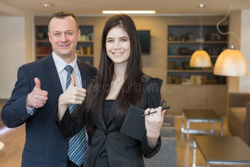 Усмехаясь человек и женщина в делать деловых костюмов большие пальцы руки вверх стоковое изображение rf
