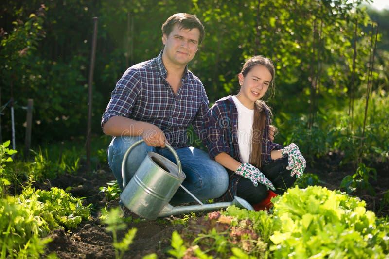 Усмехаясь человек и милая девушка работая на саде с моча чонсервной банкой стоковая фотография rf