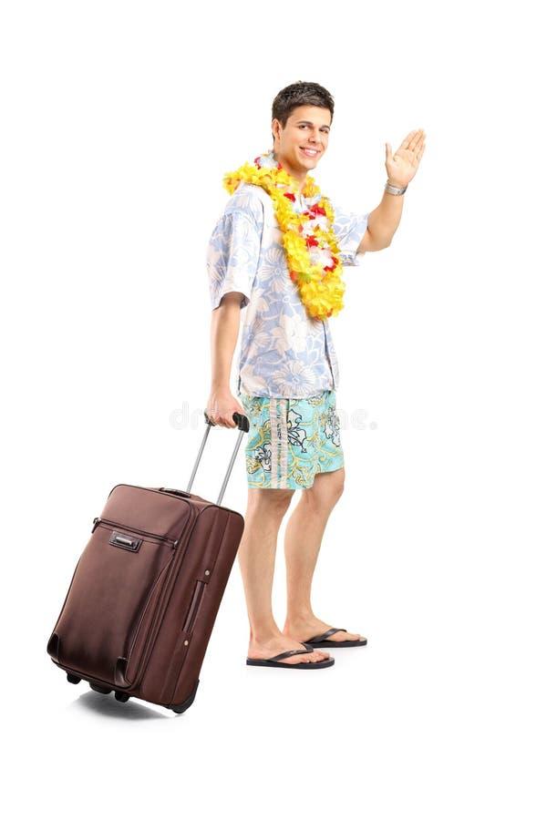 Усмехаясь человек нося его багаж и развевая до свидания стоковое изображение rf