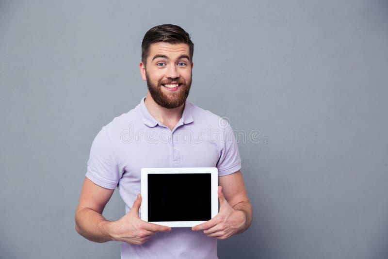 Усмехаясь человек показывая пустой экран планшета стоковое фото rf