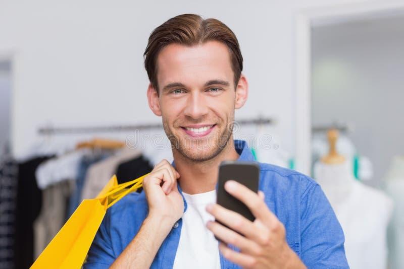 Усмехаясь человек при хозяйственные сумки смотря его smartphone стоковое изображение rf