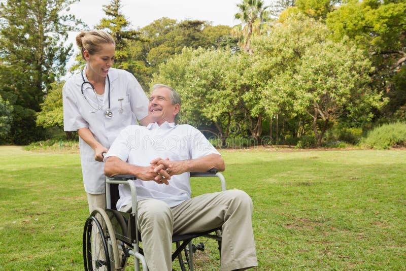 Усмехаясь человек сидя в кресло-коляске разговаривая с его pushi медсестры стоковые изображения rf