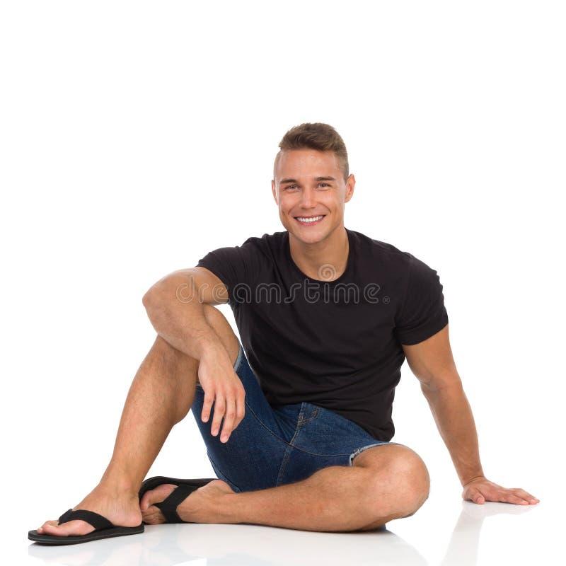 Усмехаясь человек сидя на поле и отдыхать стоковая фотография