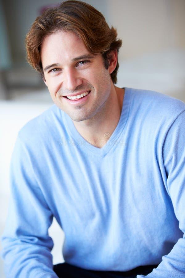 Усмехаясь человек сидя на софе стоковая фотография rf