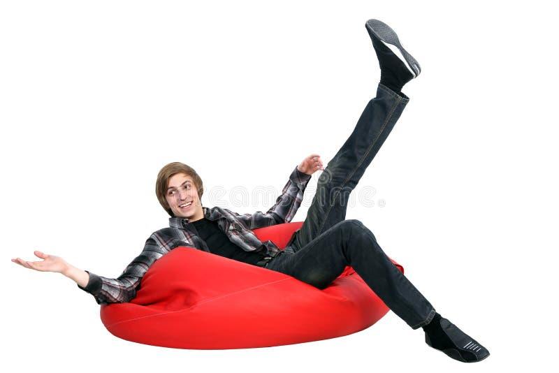 Усмехаясь человек сидя на сумке фасоли стоковое изображение rf