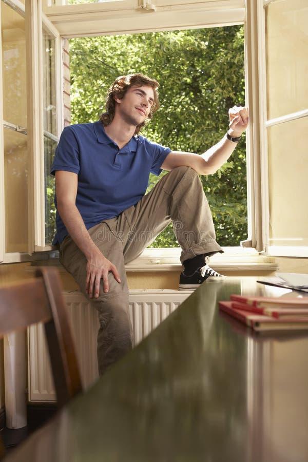 Усмехаясь человек смотря прочь на силле окна в комнате исследования стоковые фотографии rf