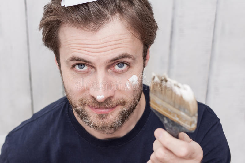 Усмехаясь человек с кистью - реновацией стоковое фото
