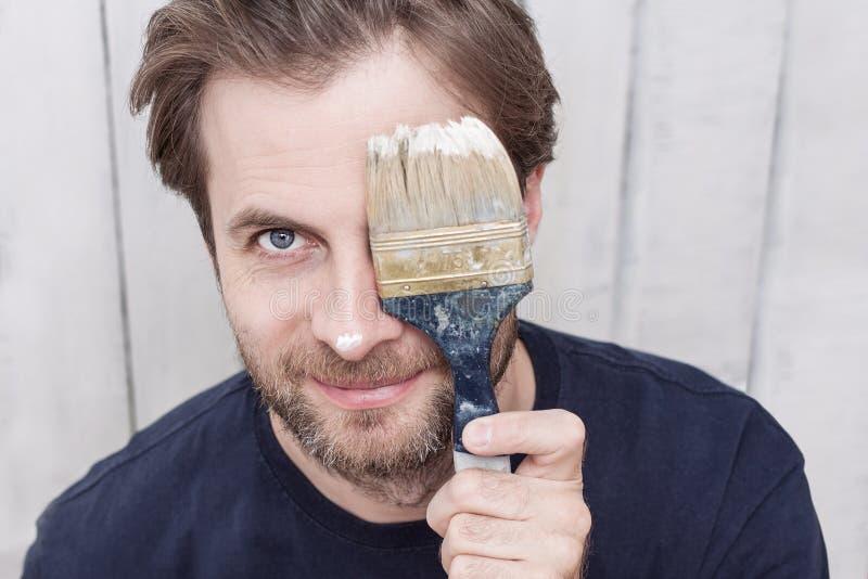 Усмехаясь человек с кистью - реновацией стоковое фото rf