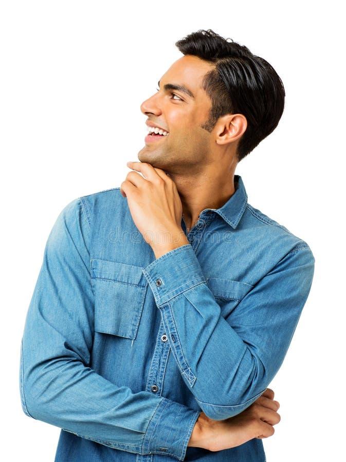 Усмехаясь человек с рукой на Chin смотря прочь стоковое изображение