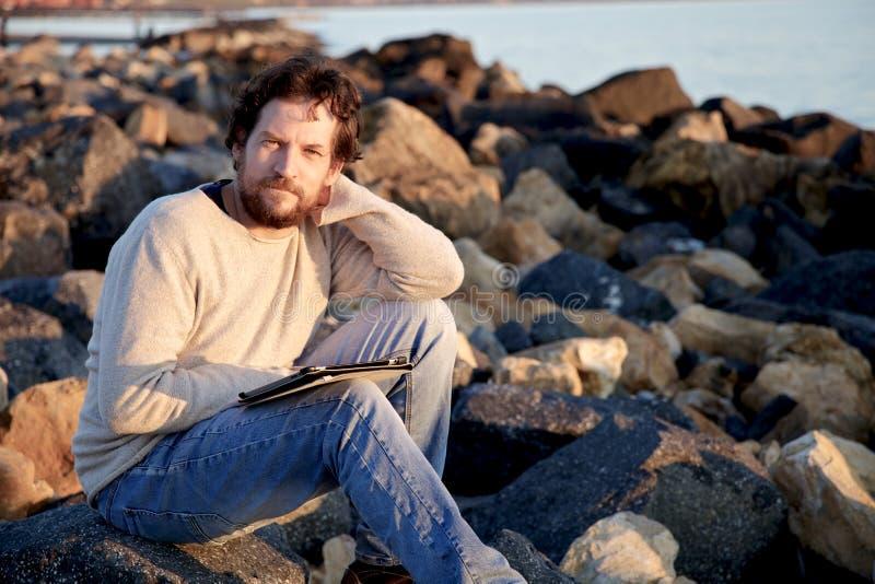 Усмехаясь человек с таблеткой на пляже с утесами стоковое фото rf