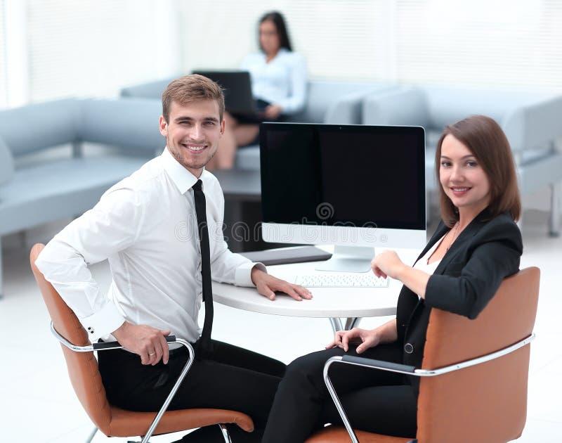Усмехаясь член дела объединяется в команду сидеть на столе стоковые изображения