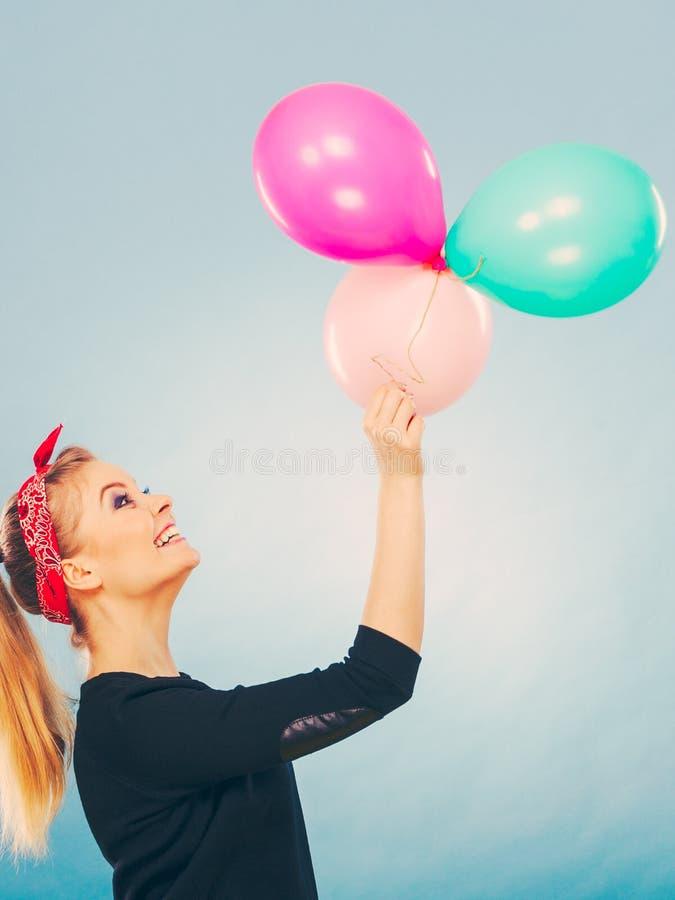 Усмехаясь шальная девушка имея потеху с воздушными шарами стоковое изображение rf