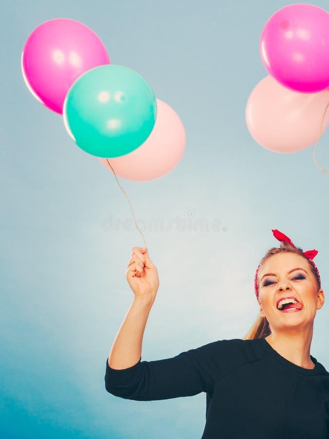 Усмехаясь шальная девушка имея потеху с воздушными шарами стоковые фото