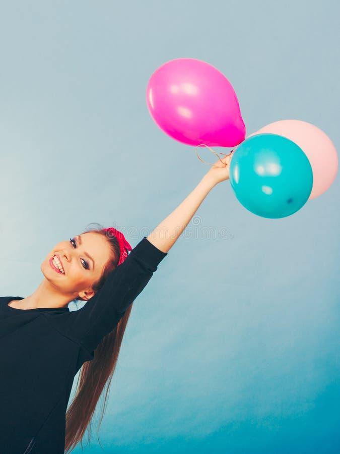 Усмехаясь шальная девушка имея потеху с воздушными шарами стоковое фото rf