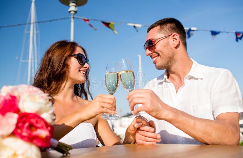 Усмехаясь шампанское пар выпивая на кафе стоковые изображения rf