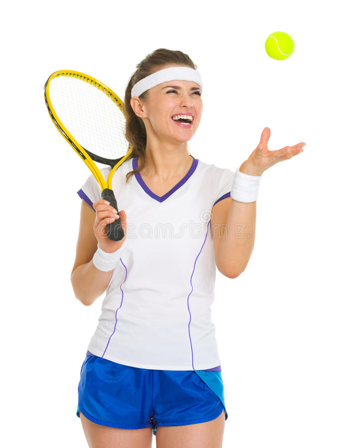 Усмехаясь шарик женского теннисиста бросая вверх стоковые фотографии rf
