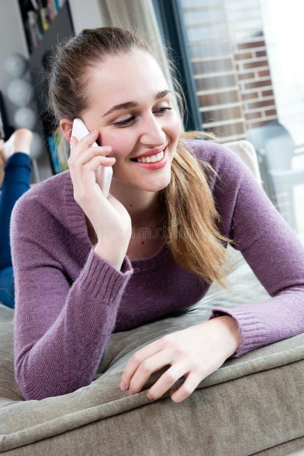 Усмехаясь шикарная молодая женщина говоря на ее smartphone, лежа вниз стоковая фотография