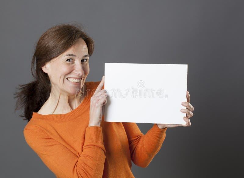 Усмехаясь шикарная середина постарела женщина держа белую панель маркетинга потехи стоковые изображения