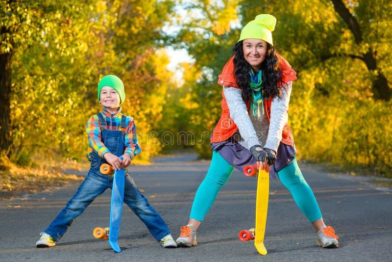 Усмехаясь ширина женщины и мальчика стоящая красит пластмассу стоковые фотографии rf