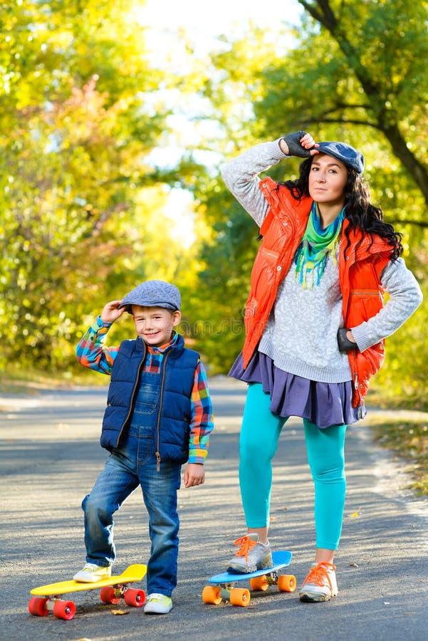 Усмехаясь ширина женщины и мальчика стоящая красит пластмассу стоковые изображения rf