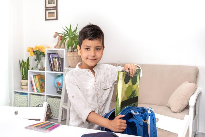 Усмехаясь школьник собирает портфель в школе, добавляет папку для ученических книг стоковое фото rf