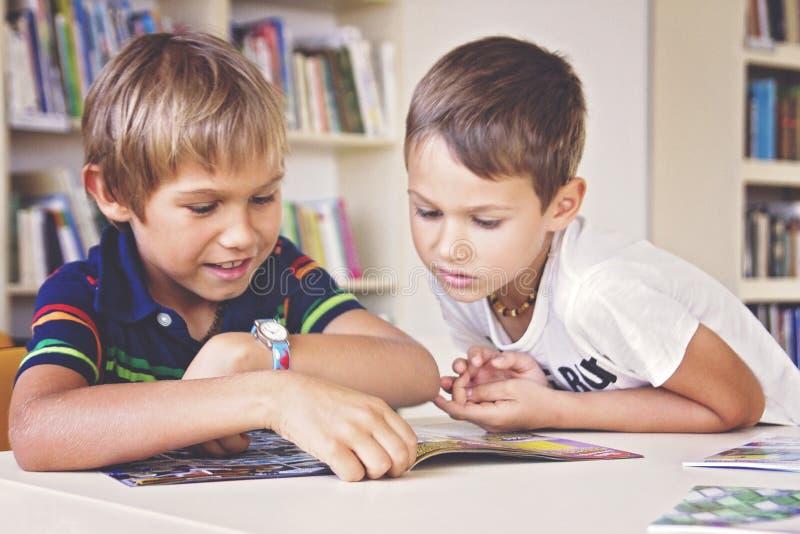 Усмехаясь школа ягнится книга сидеть и чтения в библиотеке стоковое фото rf