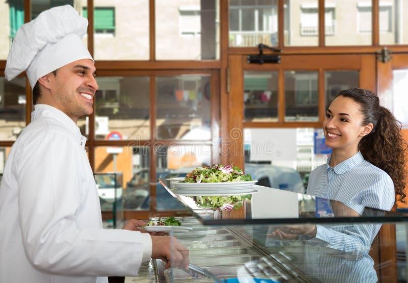 Усмехаясь штат и женский клиент на счетчике стоковая фотография rf