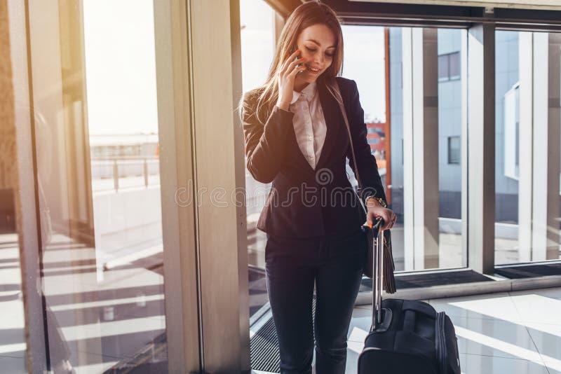 Усмехаясь элегантная женщина идя с ее багажем в авиапорте говоря на smartphone стоковое изображение