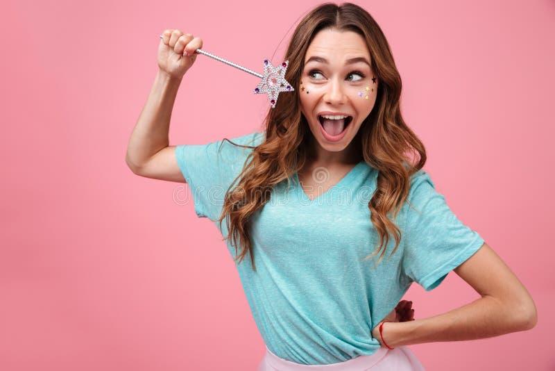 Усмехаясь эмоциональная молодая женщина держа волшебно звезду ручки стоковое фото rf