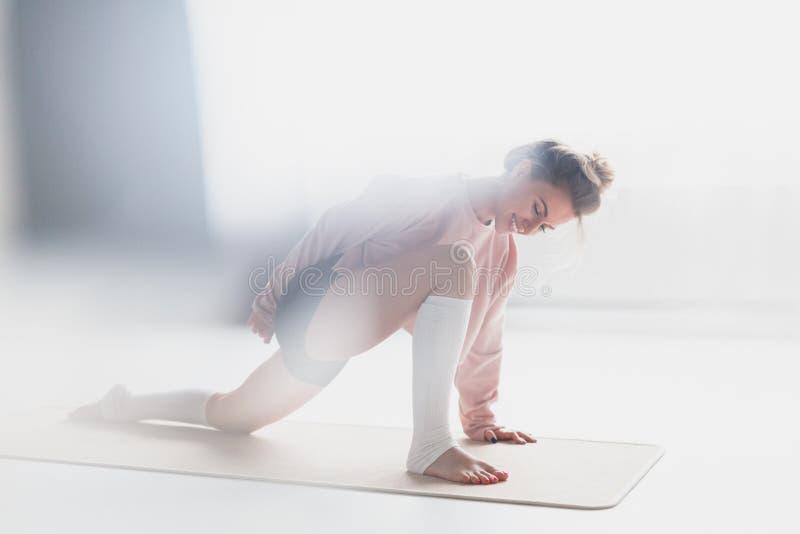 Усмехаясь asana йоги тренировки женщины на циновке стоковое фото