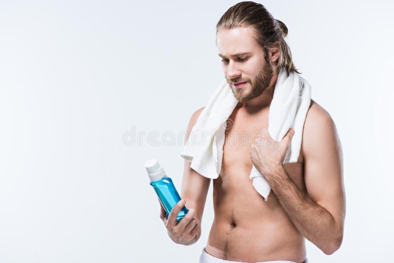 Усмехаясь beardedman с полотенцем вокруг шеи держа rinse зуба в руке и смотря на ем, стоковое фото