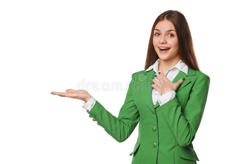 Усмехаясь excited показ женщины раскрывает ладонь руки с космосом экземпляра для продукта или текста Бизнес-леди в зеленом костюм стоковые фото
