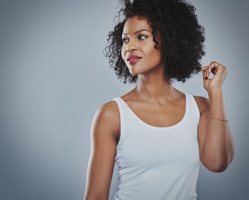 Усмехаясь flirting женщина в белой верхней части, серой предпосылке стоковые изображения rf