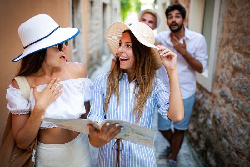 Усмехаясь gorup друзей с картой Туризм, перемещение, отдых, праздники и концепция приятельства стоковые изображения rf