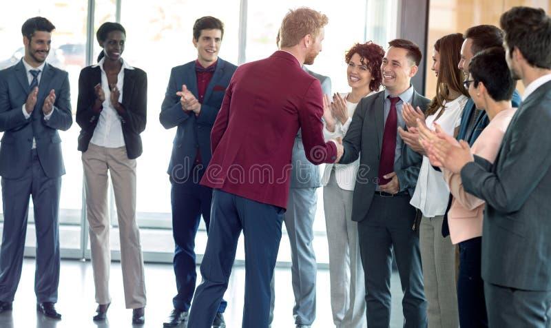 Усмехаясь handshaking деловых партнеров в знаке успешный общаться стоковое фото rf