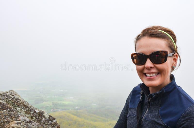 Усмехаясь hiker женщины представляет на маленьком каменистом человеке гора обозревает поход во время туманного весеннего дня Отри стоковая фотография rf