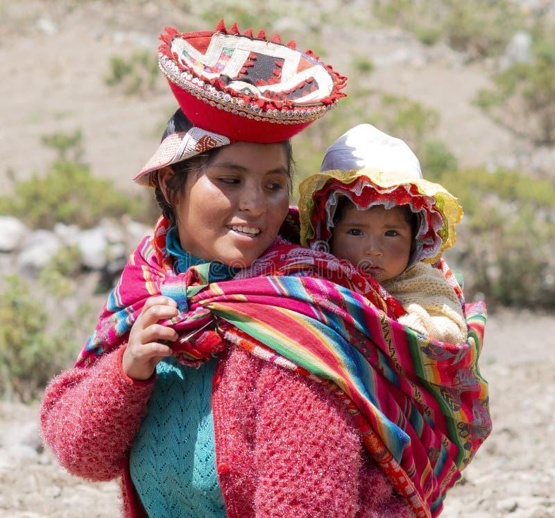 Усмехаясь Quechua женщина одетая в красочном традиционном Handmade обмундировании нося ее младенца в слинге стоковые изображения