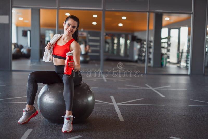 Усмехаясь sportive женщина сидя на шарике медицины стоковое фото